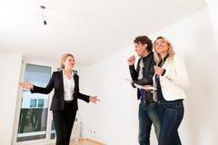 Pares jovenes que buscan las propiedades inmobiliarias con agente inmobiliario femenino Fotos de archivo