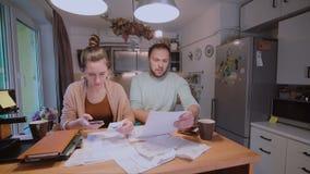 Pares jovenes que calculan su presupuesto nacional junto en la cocina, intento al dinero seguro, teniendo tensiones almacen de metraje de vídeo
