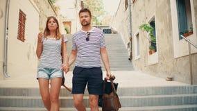 Pares jovenes que caminan abajo de la calle mediterránea peatonal de la ciudad el vacaciones Fotografía de archivo libre de regalías