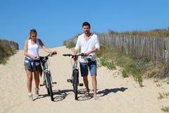 Pares jovenes que caminan con las bicis en la arena Imagen de archivo