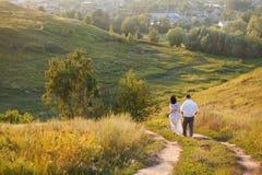 Pares jovenes que caminan en colinas Imagenes de archivo