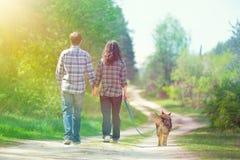 Pares jovenes que caminan en el camino rural Fotos de archivo