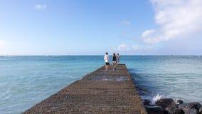 Pares jovenes que caminan en el embarcadero del mar en Honolulu, Oahu, Hawaii fotografía de archivo