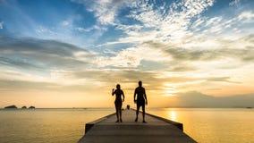 Pares jovenes que caminan en el embarcadero en el mar en la puesta del sol Imagen de archivo