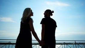 Pares jovenes que caminan en la costa que se detiene mano, par romántico en el rayo de sol, amor en aire metrajes
