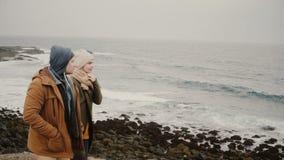 Pares jovenes que caminan en la orilla del mar junto Varón y hembra que viajan una fecha romántica cerca del agua almacen de metraje de vídeo