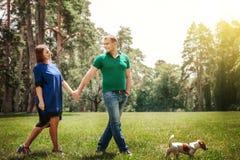 Pares jovenes que caminan en parque con el perro que lleva a cabo las manos esposa con caminar del marido al aire libre con el pe Fotos de archivo libres de regalías