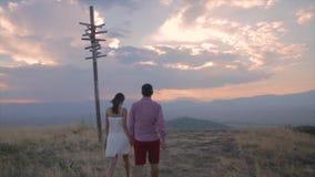Pares jovenes que caminan en puesta del sol asombrosa de la montaña metrajes