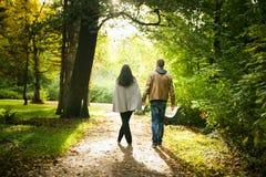 Pares jovenes que caminan en un parque de la caída Foto de archivo libre de regalías