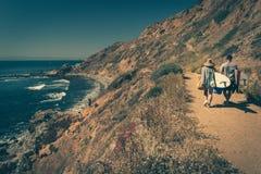 Pares jovenes que caminan en un rastro rugoso con sus tablas hawaianas Foto de archivo libre de regalías
