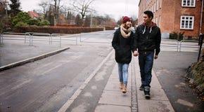 Pares jovenes que caminan en una acera Fotos de archivo libres de regalías