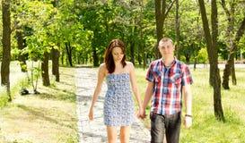 Pares jovenes que caminan junto en un parque Fotografía de archivo libre de regalías
