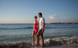 Pares jovenes que caminan a lo largo de la costa Imagen de archivo