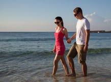 Pares jovenes que caminan a lo largo de la costa Fotos de archivo