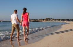 Pares jovenes que caminan a lo largo de la costa Imagen de archivo libre de regalías