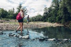 Pares jovenes que caminan a lo largo de la costa del río de la montaña en verano Muchacha que vadea a través del río Imagen de archivo libre de regalías