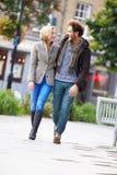 Pares jovenes que caminan a través de parque de la ciudad junto Imagen de archivo