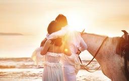 Pares jovenes que caminan un caballo majestuoso - paisaje de la playa imagen de archivo libre de regalías