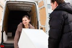 Pares jovenes que cargan un carro móvil Imagen de archivo libre de regalías