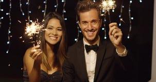 Pares jovenes que celebran Año Nuevo con las bengalas Imagenes de archivo