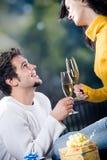 Pares jovenes que celebran acontecimiento con los vidrios y los regalos del champán Fotos de archivo
