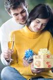 Pares jovenes que celebran acontecimiento con los vidrios y los regalos del champán Imagenes de archivo