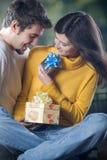 Pares jovenes que celebran acontecimiento con los vidrios y los regalos del champán Fotografía de archivo libre de regalías