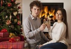 Pares jovenes que celebran días de fiesta de la Navidad Fotos de archivo