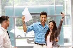 Pares jovenes que celebran la compra de un coche en la sala de exposición del coche Imagen de archivo