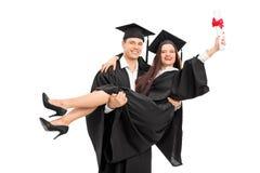 Pares jovenes que celebran su graduación Foto de archivo libre de regalías