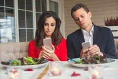Pares jovenes que cenan romántico en el apego del teléfono del restaurante fotos de archivo