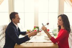 Pares jovenes que cenan romántico en el regalo color de rosa de la flor del restaurante imagenes de archivo