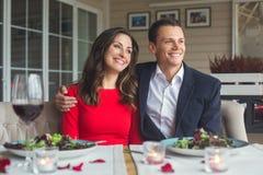 Pares jovenes que cenan romántico en el restaurante que se sienta junto pareciendo hacia fuera la ventana imagen de archivo