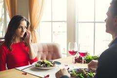 Pares jovenes que cenan romántico en la llamada de teléfono seria del restaurante imagen de archivo libre de regalías