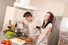 Pares jovenes que cocinan en cocina junto Foto de archivo libre de regalías