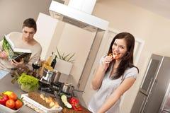 Pares jovenes que cocinan en cocina moderna Foto de archivo