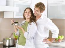 Pares jovenes que cocinan junto Imagenes de archivo