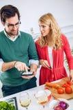 Pares jovenes que cocinan junto Foto de archivo libre de regalías