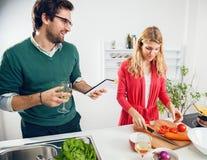 Pares jovenes que cocinan junto Imágenes de archivo libres de regalías
