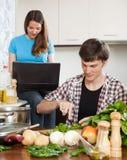 Pares jovenes que cocinan la comida Foto de archivo libre de regalías