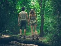 Pares jovenes que colocan en un inicio de sesión el bosque Foto de archivo libre de regalías