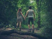 Pares jovenes que colocan en un inicio de sesión el bosque Fotografía de archivo libre de regalías