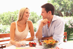 Pares jovenes que comen al aire libre Foto de archivo libre de regalías