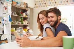 Pares jovenes que comen el desayuno mientras que usa los teléfonos móviles Imágenes de archivo libres de regalías