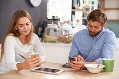Pares jovenes que comen el desayuno mientras que usa los teléfonos móviles Foto de archivo libre de regalías