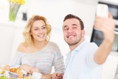 Pares jovenes que comen el desayuno y que toman el selfie foto de archivo