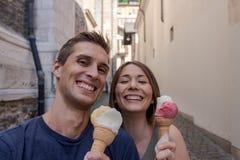 Pares jovenes que comen el helado en un callej?n imágenes de archivo libres de regalías
