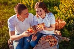 Pares jovenes que comen la pizza y que charlan afuera Mujer y hombre que tienen comida campestre en la puesta del sol lifestyle imagen de archivo libre de regalías
