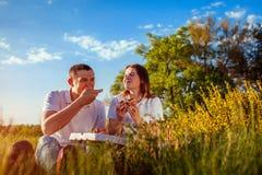 Pares jovenes que comen la pizza y que charlan afuera Mujer y hombre que tienen comida campestre en la puesta del sol lifestyle foto de archivo libre de regalías
