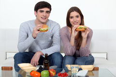 Pares jovenes que comen las hamburguesas Imagenes de archivo